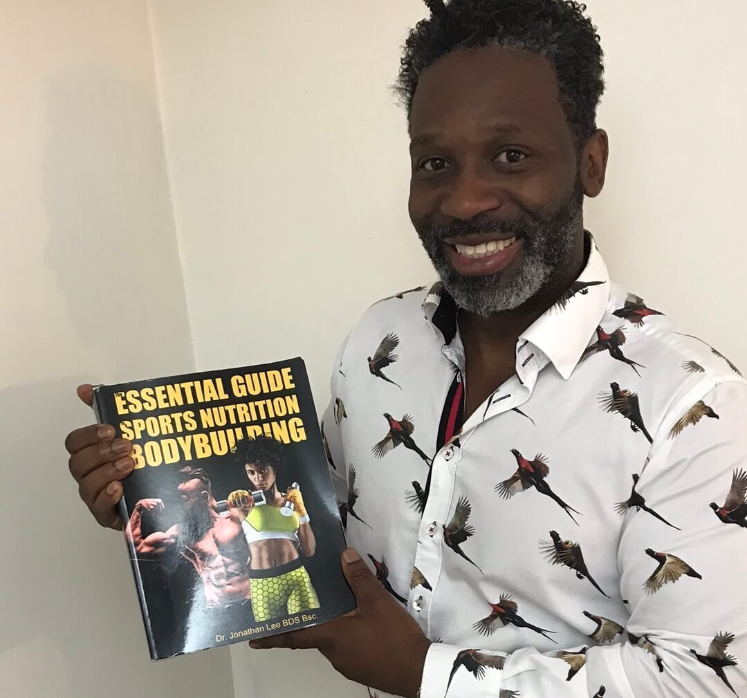man holding fitness book